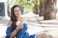 Young woman sitting in park with ice cream cone, Barcelona, Spain - CUF36521