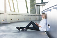 Young businesswoman sitting on floor with smartphone outside office building - CUF36524