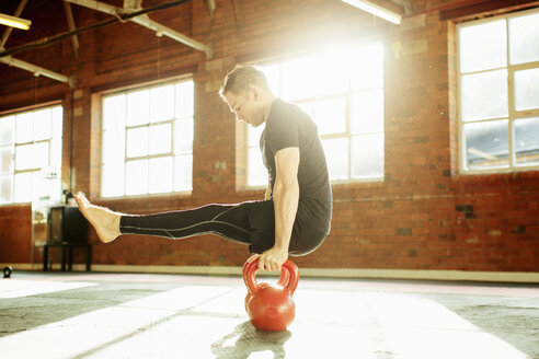 Man strength training with kettle bells - CUF36584