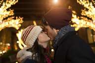 Young couple kissing on street at christmas - ISF14442