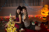 Young couple taking selfie in sitting room at christmas - ISF14445