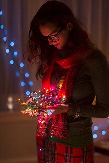 Young woman holding tangle of christmas lights - ISF14448