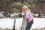 Young girl climbing wire fence in field - ISF14478