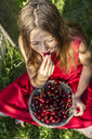 Girl sitting on a meadow eating cherries - SARF03814
