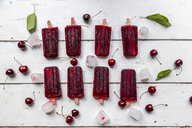 Homemade cherry ice lollies, ice cubes and cherries on white wood - SARF03823