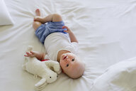 Baby girl lying on bedclothes with soft toy - CUF36754