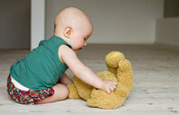 Baby girl playing with teddy bear on floor - CUF36760