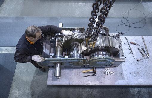 Overhead view of engineer repairing industrial gearbox in factory - CUF36766