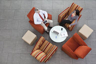Overhead view of interview in office atrium - CUF36799