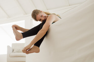 Woman dangling legs over sofa - CUF36877
