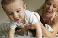 Mother guiding baby boy crawling on bed - CUF36880