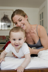 Mother guiding baby boy crawling on bed - CUF36883