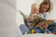 Mature mother and baby daughter on sitting room sofa reading storybook - CUF36892