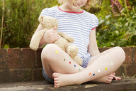 Girl on garden seat with star stickers on legs - CUF36907