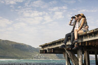 Young couple sitting on edge of old pier looking through binoculars, Cape Town, Western Cape, South Africa - CUF36949