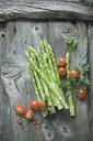 Green asparagus, parsley, tomatoes and mixed peppercorns on wood - ASF06189