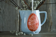 Hand-painted Easter egg hanging in front of light blue jar - ASF06198