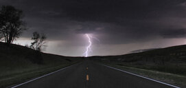 A single cloud-to-ground bolt lands at the end of a rural road, Lexington, Nebraska, USA - CUF36958