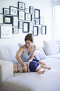 Mid adult mother tickling toddler daughter on sofa - CUF36976