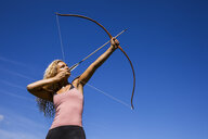 Archeress aiming with bow against blue sky - TCF05497