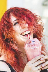 Portrait of laughing woman drinking smoothie - WPEF00484