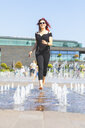 Young woman having fun running through a fountain - WPEF00487