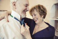 Mature woman putting bow tie on senior man - CUF37027
