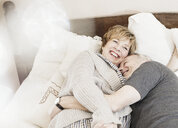 Couple lying on bed laughing - CUF37051