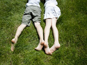 Overhead view of brother and sisters legs as they lay on grass - CUF37060