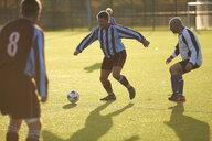 Football players running after ball - CUF37099