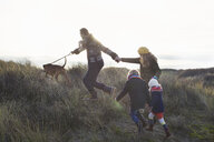 Mid adult couple strolling in sand dunes with their son, daughter and dog - CUF37126