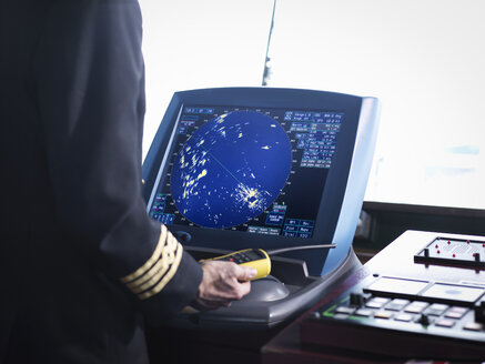 Ship's captain working on bridge with radar screen, close up - CUF37192