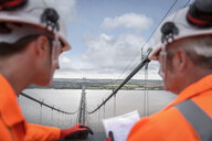 Bridge workers on top of suspension bridge. The Humber Bridge, UK was built in 1981 and at the time was the world's largest single-span suspension bridge - CUF37219