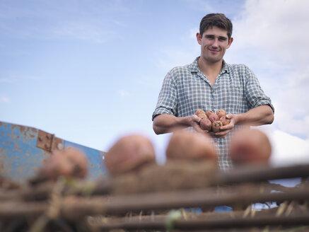 Portrait of farmer holding crop of organic potatoes - CUF37252