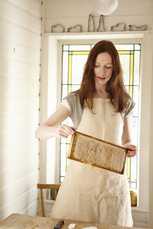 Female beekeeper in kitchen holding up