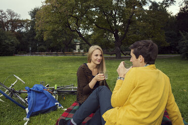 Young couple drinking wine on picnic blanket in park - CUF37324