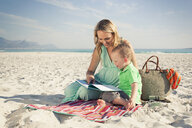 Mid adult mother reading with young son on beach, Cape Town, Western Cape, South Africa - CUF37339