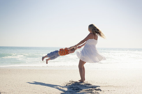 Mid adult mother swinging young son by hands on beach, Cape Town, Western Cape, South Africa - CUF37342