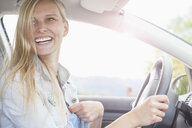 Young woman smiling behind wheel of car - CUF37366