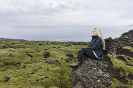 Mid adult woman sitting on rocks, looking at view, Blafjoll, Iceland - CUF37375