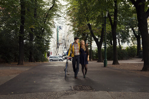 Young couple strolling in tree lined park - CUF37381