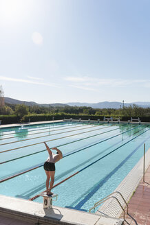 Mid adult man preparing to dive into swimming pool, Sardinia, Italy - CUF37447