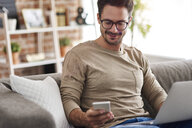 Smiling man sitting on couch at home using laptop and cell phone - ABIF00657