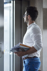 Businessman with magazines entering the elevator - ABIF00663
