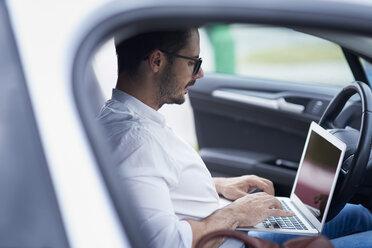 Businessman sitting in car working on laptop - ABIF00669