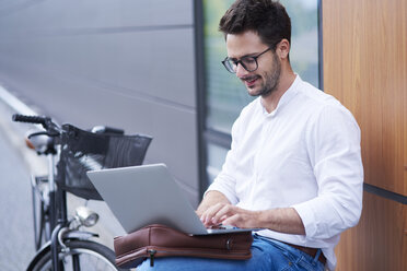 Businessman with bicycle using laptop outdoors - ABIF00672