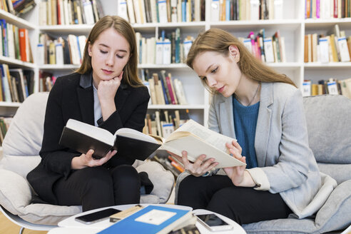 Two teenage girls sitting in a public library reading books - WPEF00492