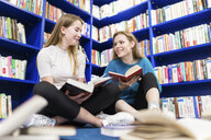Two teenage girls with books sitting on the floor in a public library - WPEF00513