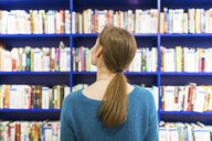 Back view of teenage girl in a public library looking for a book - WPEF00516