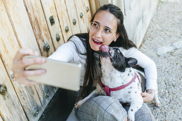 Young woman using smartphone, taking a selfie with her dog - KIJF01956